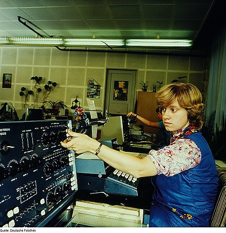 A woman operates a Linotron 505, a cathode ray tube phototypesetting machine. Dresden, 1983.