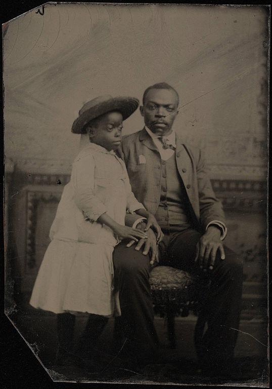 file full length double portrait  seated man wearing three piece suit  child in straw hat and