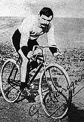 A signed postcard of a man on a bicycle on a sandy road.