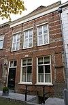 foto van Huis onder met rode pannen belegd schilddak en met gebosseerd gepleisterde lijstgevel