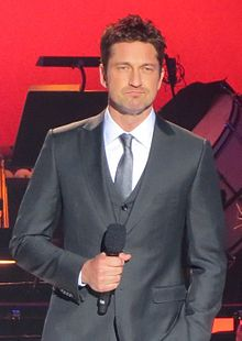 Gerard Butler standing with a microphone with a red background in a suit and tie facing the camera