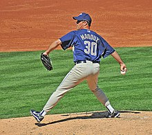 "A man in a navy blue baseball jersey prepares to throw a baseball from a pitcher's mound with his right hand. His jersey reads ""Maddux"" in small tan print and ""30"" in larger tan print. He is wearing a navy blue baseball cap and gray baseball pants."