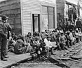 Group of Inuit natives sitting outside a building by the side of the road, Nome, Alaska, July 28, 1906 (AL+CA 2370).jpg