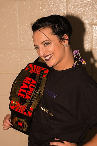 "Ruby Riott - Lovelace posing with Alpha-1's ""Alpha Male"" championship belt"