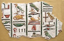 A stone fragment with brightly-painted colors and raised-relief images of Egyptian hieroglyphs, written in vertical columns, set against a beige background