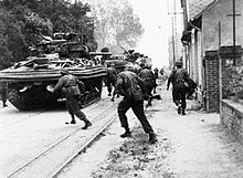 Sherman tanks and British soldiers advancing up a street