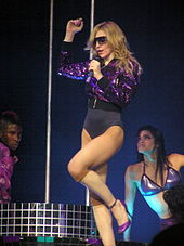 Image of a blond women. She's wearing a purple sparkly jacket and a purple leotard underneath. She's also wearing sunglasses and holds a microphone to her mouth. To her right there's a brunette female wearing a purple bra and to her left an African American male