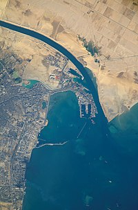 Satellite view o the port an ceety that are the soothren terminus o the Suez Canal that transits throu Egyp an debouches intae the Mediterranean Sea near Port Said. (Up is north-east).
