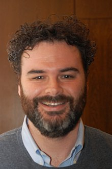 Head and shoulders photo of Greenberg smiling, with a beard and curly dark hair