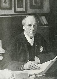 Man seated at his desk looking up at the camera