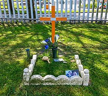 The image shows an orange wooden cross, in front of which is a small 0.5m square grass area bounded by stones, with some flowers and a small photograph of Karl.