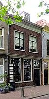foto van Pand Lage Gouwe 28 met lijstgeveltjemet in de verdieping raamhekken. Schilddak, waarin dakvenster met vleugelstukken
