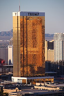 A tall rectangular-shaped tower in Las Vegas with exterior windows shimmering with 24-karat gold. It is a sunny day and the building is higher than many of the surrounding buildings, which are also towers. There are mountains in the background. This tower is called the Trump Hotel Las Vegas.