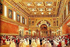 The State Ballroom is the largest room at Buckingham Palace. It was added by Queen Victoria and is used for ceremonies such as investitures and state banquets. This picture dates from 1856. The polychrome colour scheme has been replaced by mainly white decoration with gold details and red upholstery.