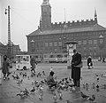 Man en kind voeren duiven op het plein met op de achtergrond een tram voor het r, Bestanddeelnr 252-8825.jpg