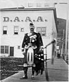 Man in a kilt holding bagpipes standing in front of the Dawson Amateur Athletic Association building at midnight, Dawson, Yukon (AL+CA 6663).jpg
