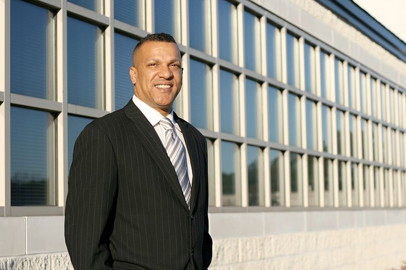 File:Man in biz suit in front of office windows.jpg