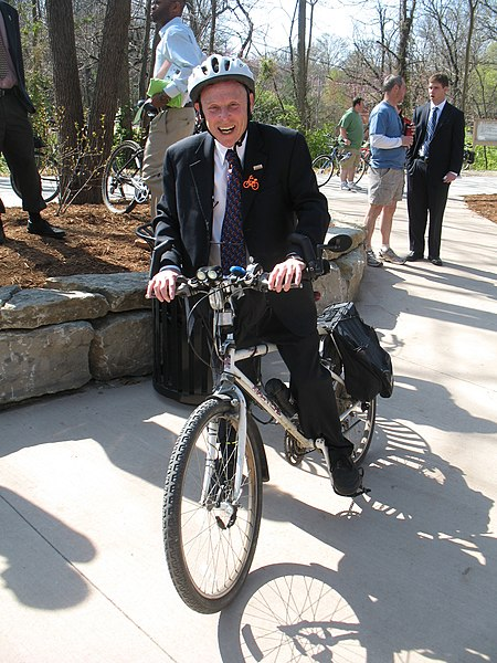 Image of a man riding a bike wearing a suit.