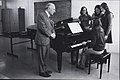 Music Education at NCPE, depicting a piano teacher with a female student playing the piano and three fellow students observing. (9370854744).jpg