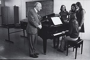 Piano pedagogy - Music Education at NCPE, depicting a piano teacher with a student playing the piano and three fellow students observing. (9370854744)