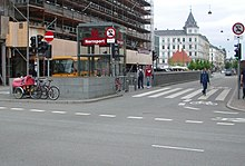 "A street intersection. In a traffic island is an elevator marked ""Nørreport"" and beside it is the top of an escalator"