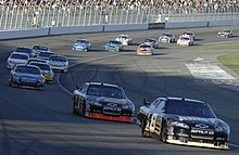 Nineteen cars photographed driving on the front stretch of the Las Vegas Motor Speedway