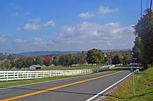 A rolling landscape with hills in the distance, a line of trees some of which are turning red, and fields in the foreground. A white fence separates them from a road that stats at bottom left and then passes between trees at the right center before cresting. At the bottom right is a small green sign with white numbers on a metal stand.