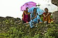 Nepali women sit on a stone wall in Dhikur Pokhari village, Kaski district, Nepal.jpg