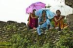 Nepali women sit on a stone wall in Dhikur Pokhari village, Kaski district, Nepal.jpg