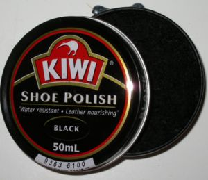 Shoe polish - An open can of shoe polish with a side-mounted opening mechanism visible at the top of the photo
