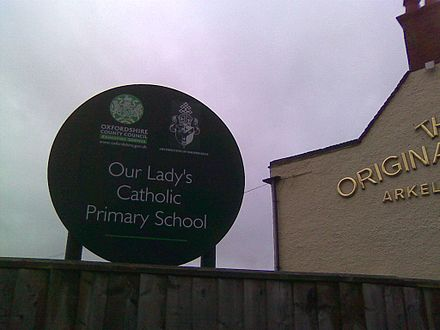 A sign for a Catholic school in Oxford, with the coat-of-arms of the Archdiocese of Birmingham and the logo of the Oxfordshire County Council. Our Lady's Catholic Primary School Oxford.jpg