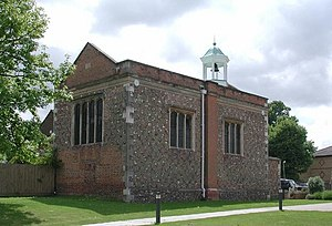 A flint and brick chapel seen from an angle, with a brick gable at the near end, and a white bellcote towards the far end