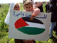 Palestinian child holds a sign on Land Day