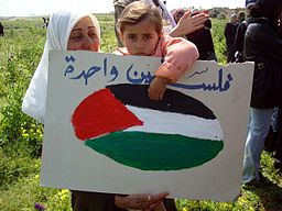Palestinian child holds a sign on Land Day.jpg
