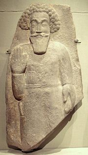 Parthian votive relief. The style displays frontally, shallow relief and attention to ornamental detail. Typical decorated costume and dagger tucked in belt. Iran, Khuzestan(?), 2nd century CE.