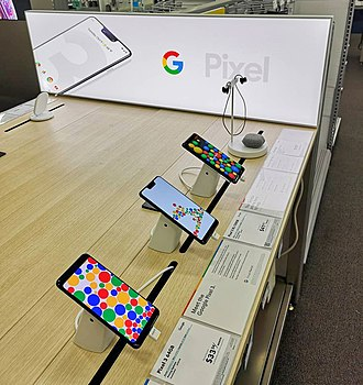 Google Pixel - Pixel 3 and Pixel 3 XL on retail display with Pixel Buds and wireless charging accessories, October 2018.