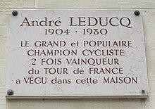 Photographie d'une plaque commémorative en pierre blanche gravée en lettres rouges.