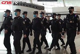 Policjanci w maskach patrolujący lotnisko Wuhan Tianhe podczas epidemii koronawirusa Wuhan.jpg