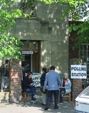United Kingdom general election, 2005 - Unofficial tellers, wearing party rosettes, sit outside polling stations collecting voter registration numbers