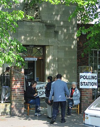 2005 United Kingdom general election - Unofficial tellers, wearing party rosettes, sit outside polling stations collecting voter registration numbers