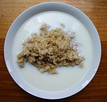 Cooked grain porridge with milk pooling around the edges of the bowl