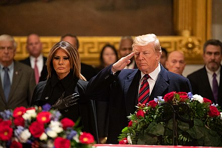 President Donald Trump salutes the casket containing the remains of George H.W. Bush as First Lady Melania Trump looks on during the lying in state on December 3, 2018. President Donald Trump salutes at the casket of former President George H. W. Bush.jpg