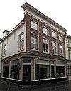 foto van Huis met eenvoudige lijstgevel in schoon werk, kroonlijst op klossen en hoog schilddak, op de hoek van de molstraat