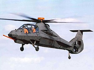 Brown helicopter with faceted surfaces flying. The two crew members inside cockpit are wearing bright orange vests