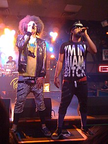 Two men clad in casual attire holding microphones whilst performing on a brightly lit stage.