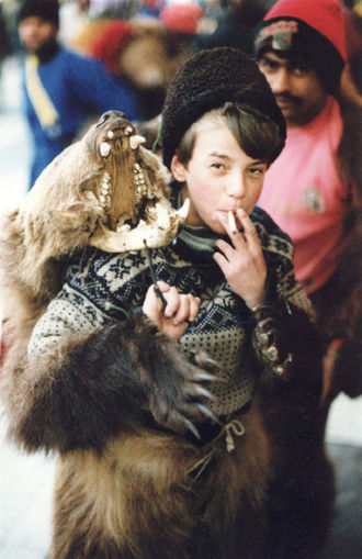Romani society and culture - Romani boy in bear costume, part of entertainer team for working Christmas crowds. Budapest, Hungary.
