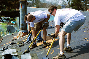 "Tar paper - Workers using special ""roofing shovels"" to remove composite shingles as part of a roof repair. Roofing felt or tar paper is here used as underlay(ment) between the wooden sheathing and exterior shingles."