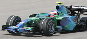 """Honda RA107 - Rubens Barrichello driving the RA107 at the 2007 Malaysian Grand Prix, with its characteristic """"Earth"""" livery."""