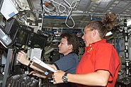 STS112 Whitson and Magnus operate the controls of Canadarm 2