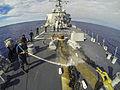 Sailors spray down the foc'sle. (12370893614).jpg